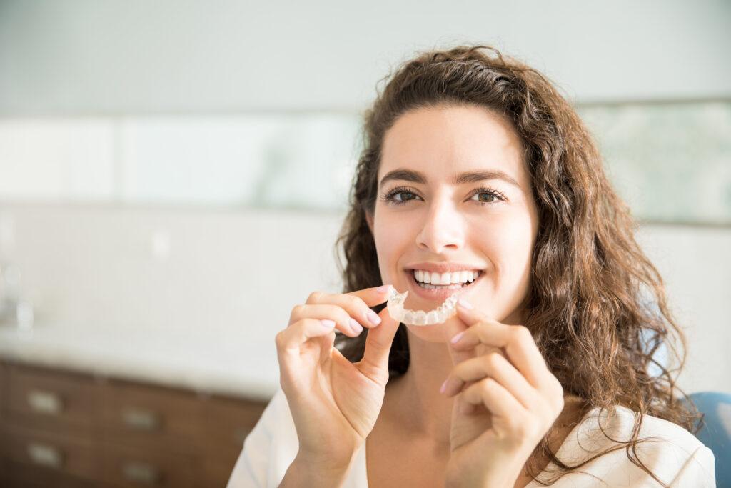 Lächelnde Frau hält eine unsichtbare Zahnschiene
