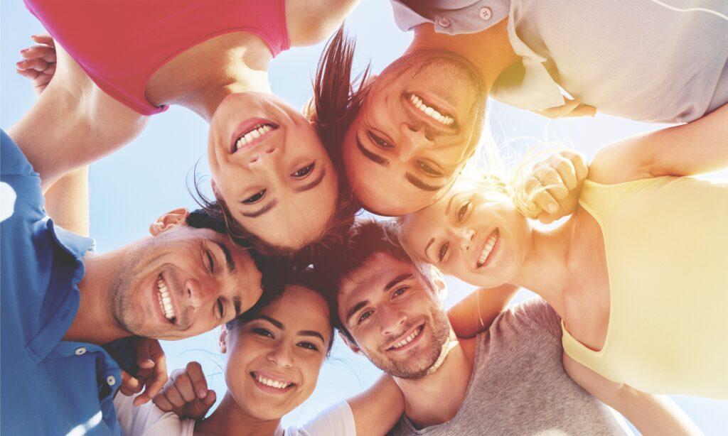 Eine Gruppe von Menschen steht im Kreis und Blick lächelnd nach unten in die Kamera