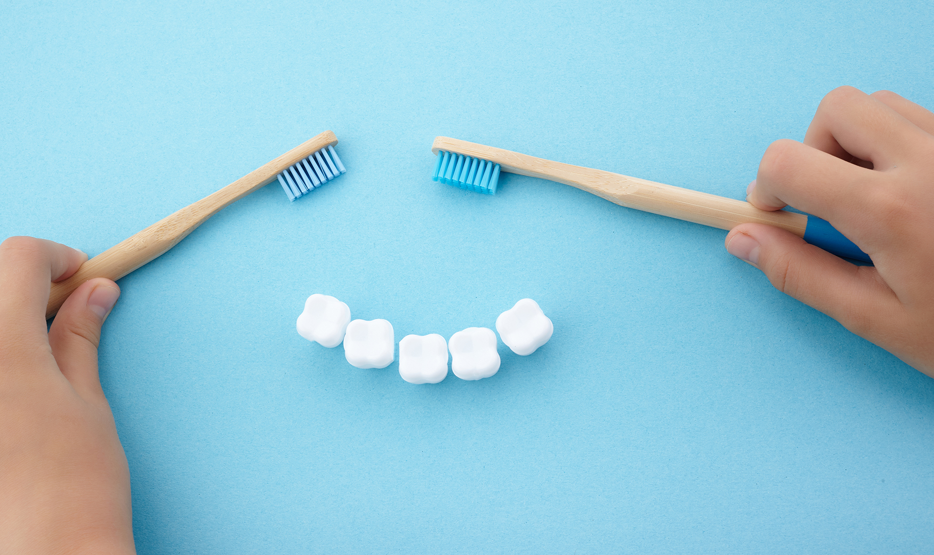 child's hand with toothbrush and white platic tooth on blue background